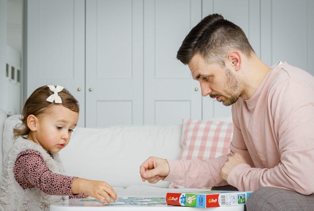 Tėtis žaidžia su dukrele prie staliuko stalo žaidimą