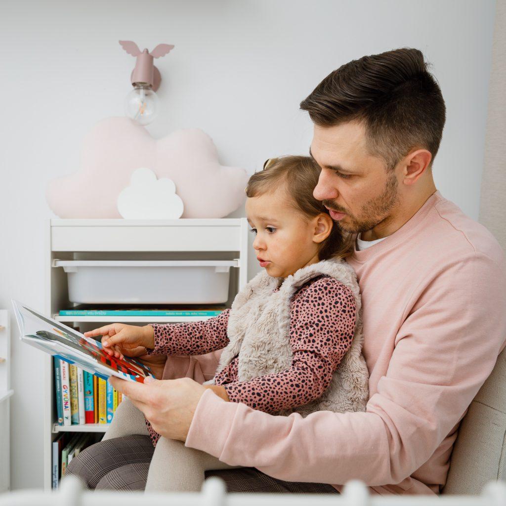 Tėtis skaito knygelę dukrai ant kelių