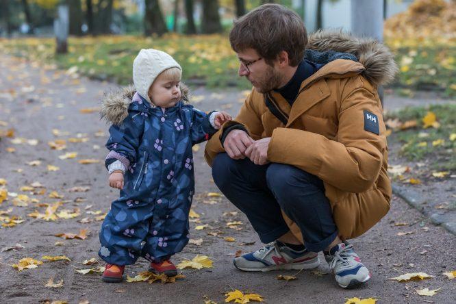 Tėtis parke pritūpęs prie savo vienerių metų dukrytės. Žiūri vienas į kitą