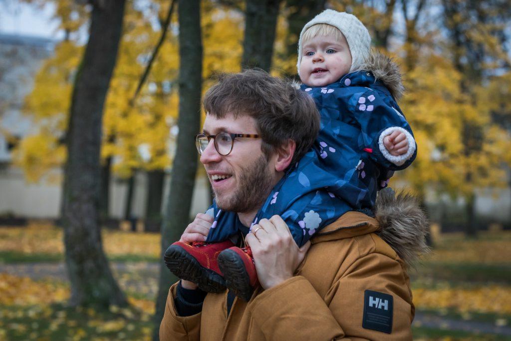 Tėtis laiko vienerių metų dukrą ant pečių