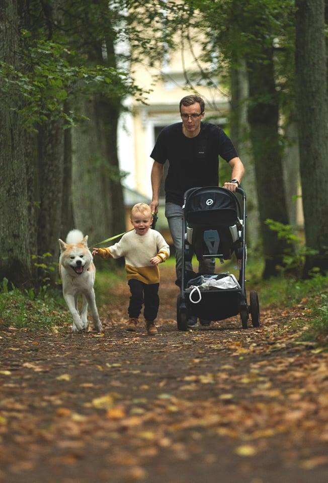Tėtis parke stumia vežimėlį, šalia eina trijų metų berniukas ir šuo
