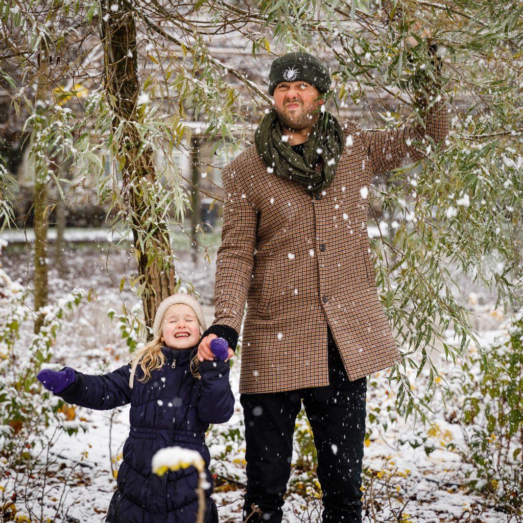 Tėtis su dukra po medžiu krato nuo jo sniegą
