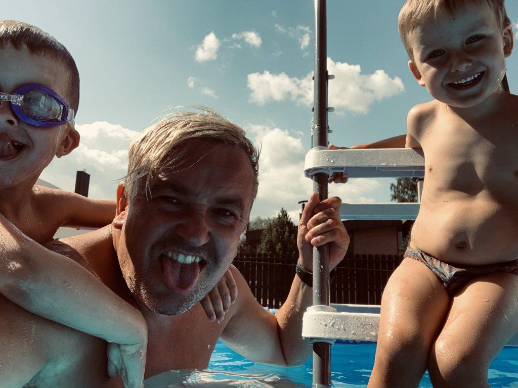 Tėtis su trimečiu ir penkiamečiu sūnumis baseine.