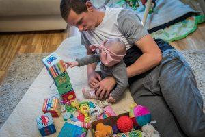 Tėtis žaidžia su 6 mėn. dukrele ant kilimo
