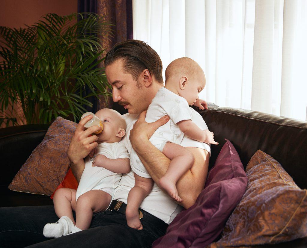 Vyras maitinantis kūdikius dvinukus ant rankų