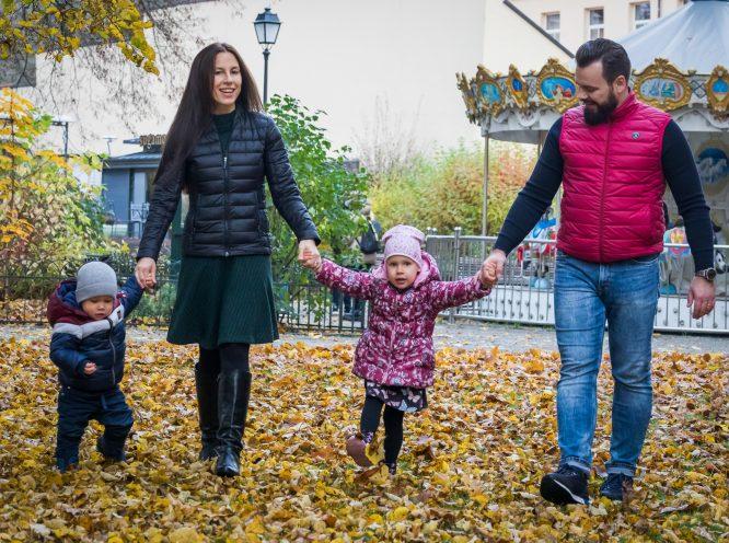 Tėtis ir mama parke su dviem mažais vaikais