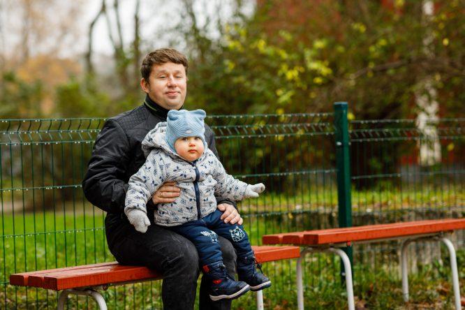 Tėtis ant kelių laiko metukų sūnų