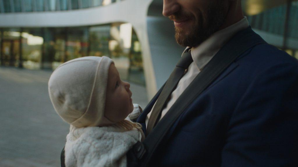 Vyras su kostiumu nešasi kūdikį nešyklėje prie ofiso pastato.