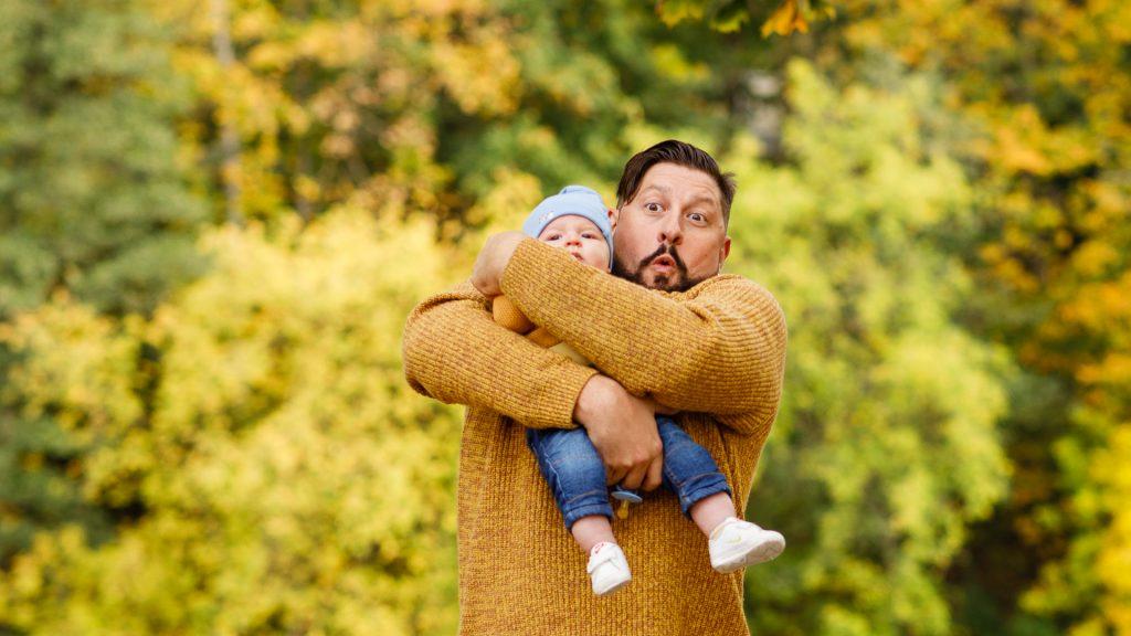 Vyras laiko kūdikį ant rankų gamotoje.