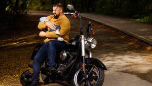 Tėtis su kūdikiu ant rankų, sėdi ant motociklo miško kelyje
