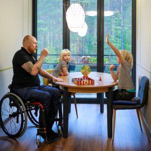 Vyras vežimėlyje sėdi prie stalo su septynmečiais dvynukais ir linksmai žaidžia stalo žaidimus