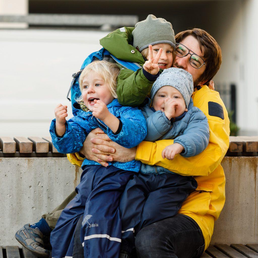 Vyras glėbyje laiko tris vaikus