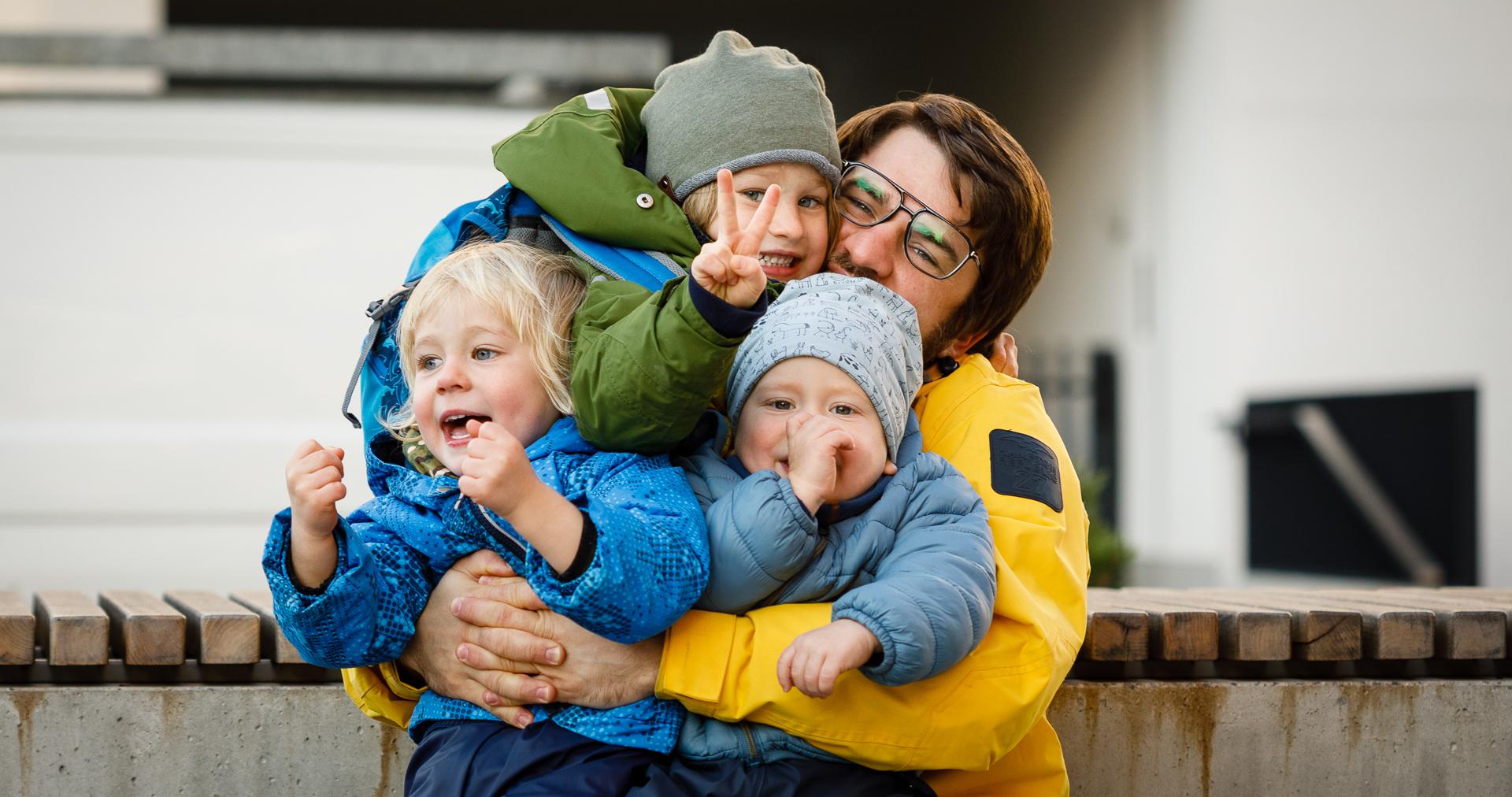 Tėtis glėbyje laiko tris sūnus