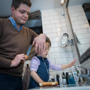 Vyras šukuoja mažai dukrai plaukus vonioje