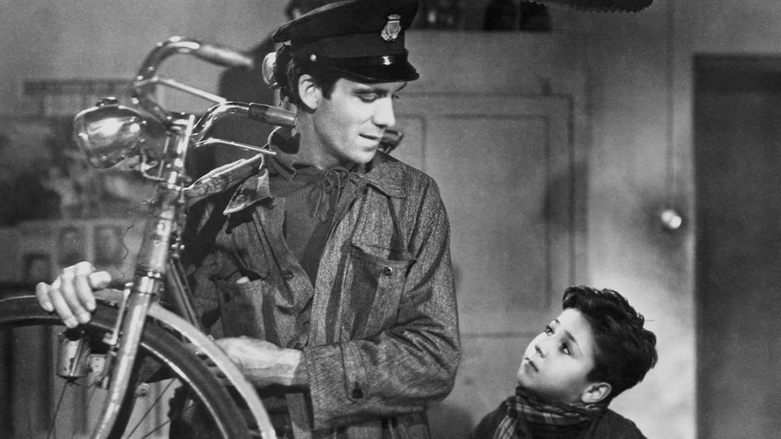 Vyras laikydamas dviratį rankose žiūri į mažą berniuką