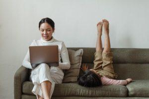 Moteris sėdi su kompiuteriu ant kelių, šalia jos guli vaikas