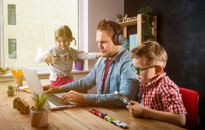 Tėtis su ausinėmis prie stalo žiūri šį kompiuterį, šalia vaikai žaidžia