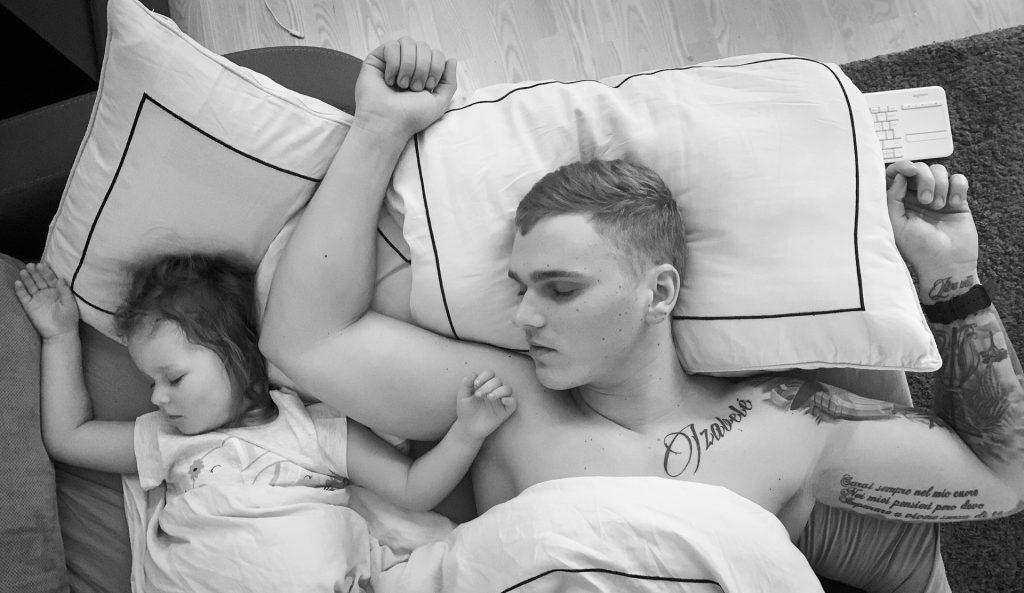Tėtis ir dukra miega, abu pakėlę rankas į viršų