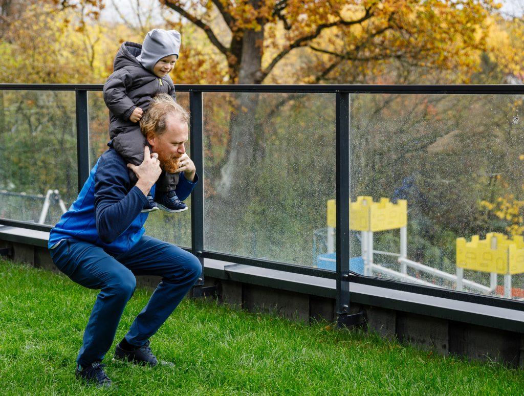 Tėtis laiko sūnų ant pečių ir daro įtupstą kieme