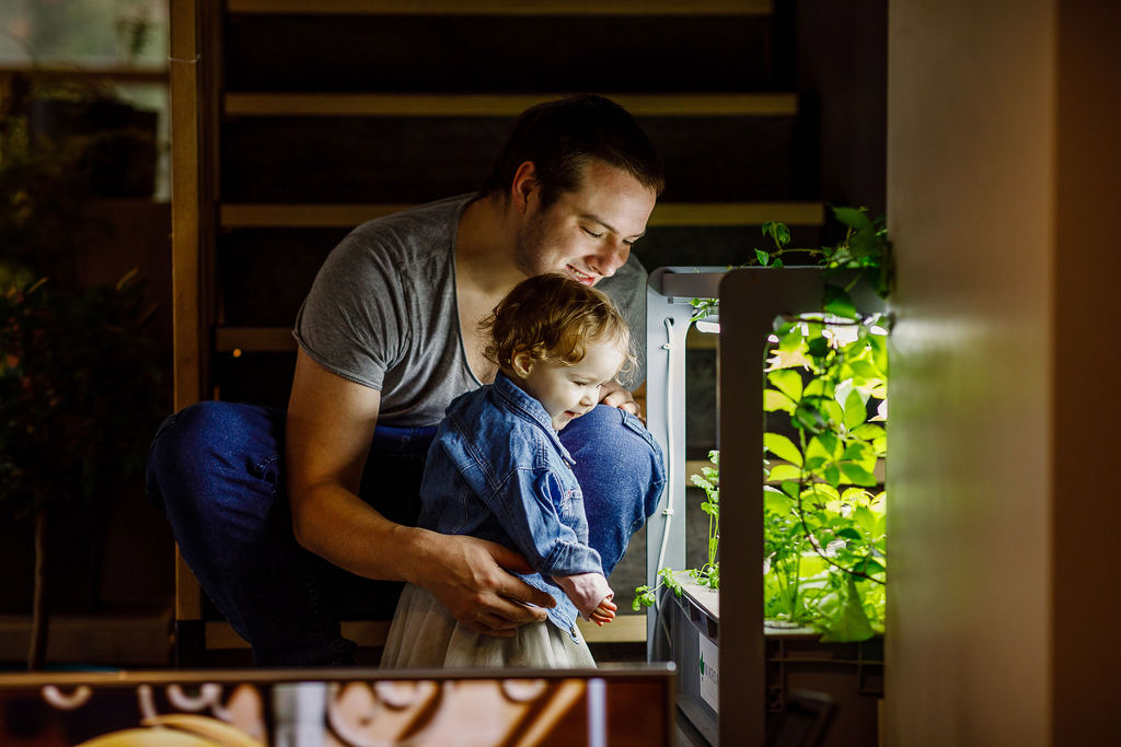 Tėtis su vienerių metų dukrele ant rankų žiūri į apšviestą akvariumą