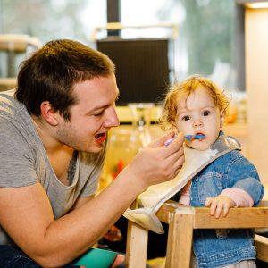 Tėtis maitina vienerių metų dukrytę