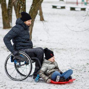 Tėtis rateliuose stumia dukrą and slidinėjimo lentos sniegu