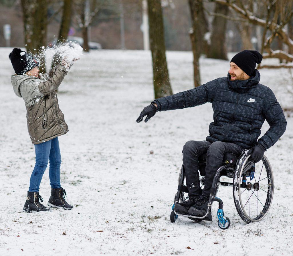Tėtis rateliuose mėtosi su dukra sniego gniūžtėmis