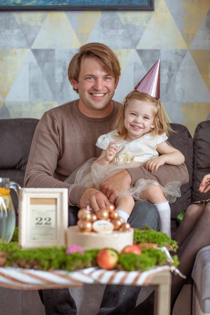 Tėtis su dukrele ant kelių gimtadienio šventėje