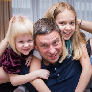 Tėtis, apsikabinęs su dviem dukromis