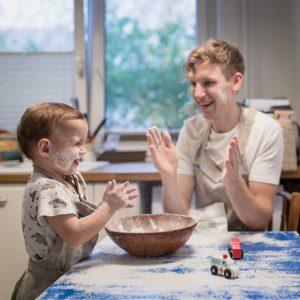 Tėtis su vienerių metukų sūnumi barstosi miltais virtuvėje