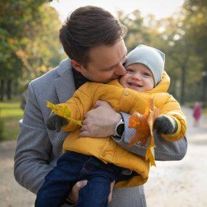 Tėtis glėbyje laiko besijuokiantį vienerių metų sūnų