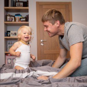 Tėtis su dukrele žaidžia ant lovos
