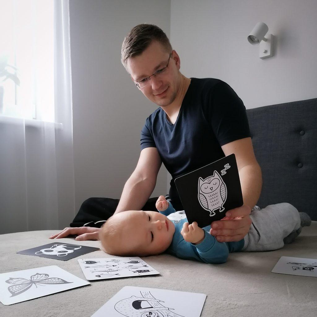Tėtis savo kūdykiui ant lovos rodo korteles su piešinukais