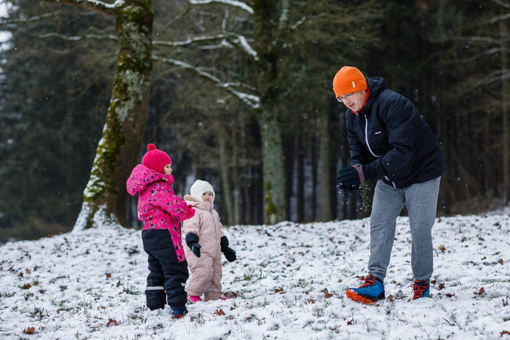 Ttėis apsnigtame miške žaidžia su dviem dukrytėmis