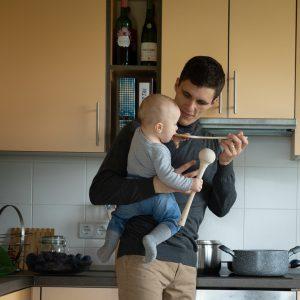 Tėtis virtuvėje ant rankų laiko sūnų, duoda šaukštu ragauti verdamą sriubą