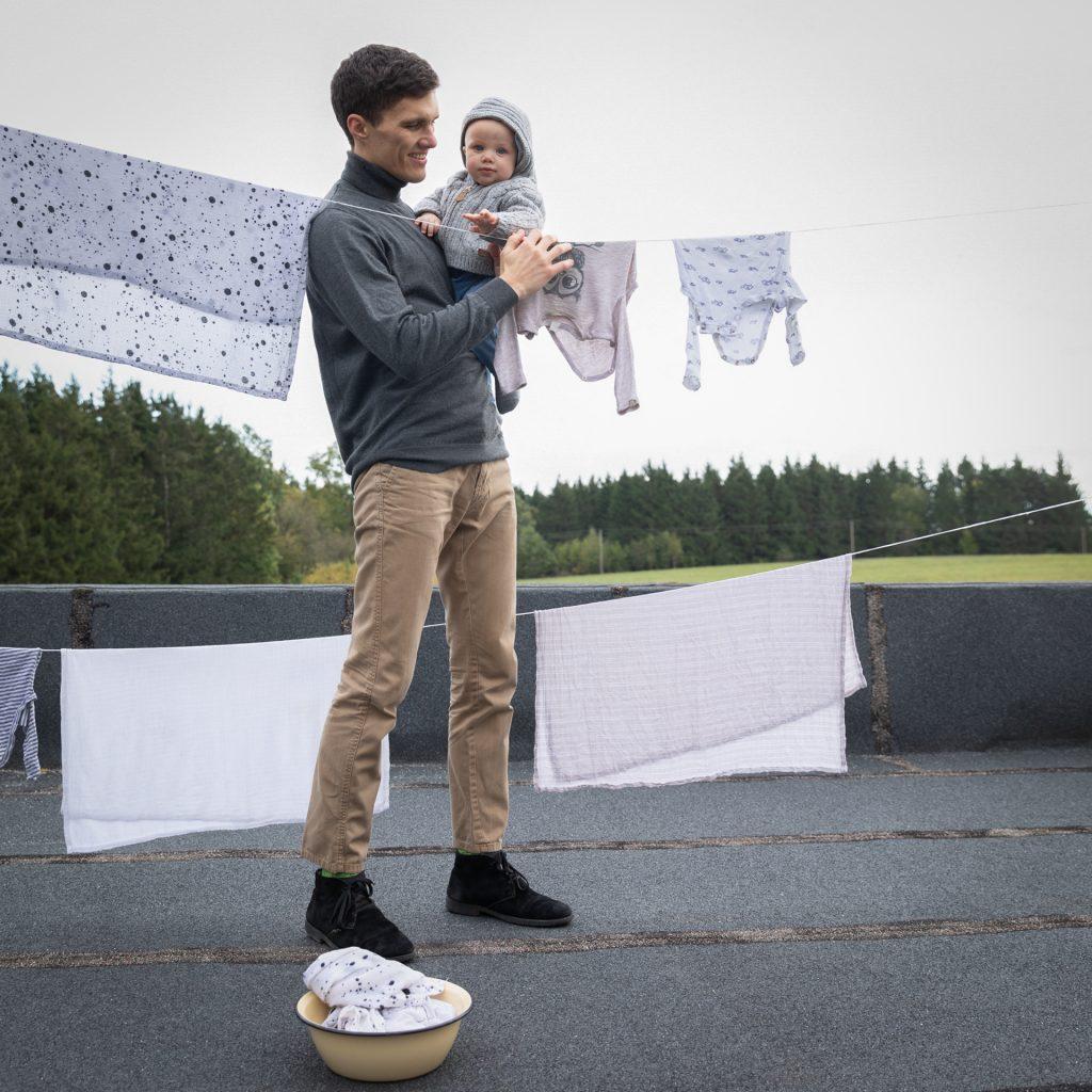 Tėtis su sūnumi ant rankų džiausto skalbinius lauke