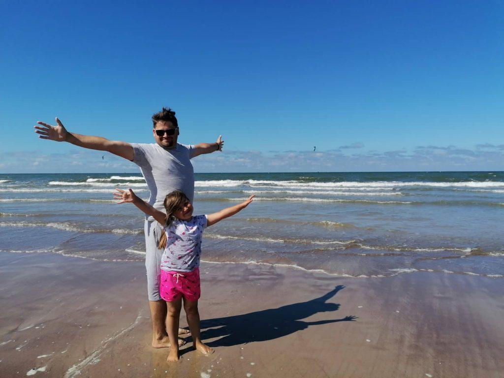 Tėtis su dukra iškeltomis rankomis į šoną prie jūros