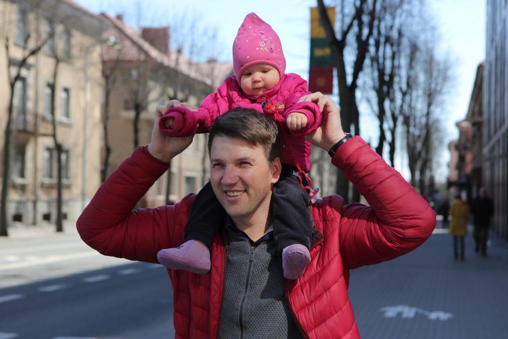 Tėtis gatvėje ant pečių laikantis dukrytę