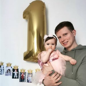 Tėtis ant rankų laiko dukrytę, už nugaros skaučiaus vienas formos balionas