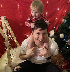 Tėtis laiko dukrytę ant pečių, abu juokiasi