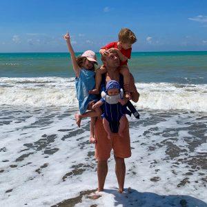 Tėtis, įbridęs į jūrą, ant rankų laiko tris vaikus