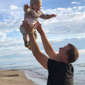 Tėtis papludimyje iškėlęs virš galvos vienerių metų kūdikį, abu juokiasi