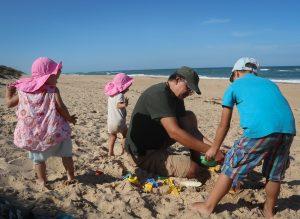 Tėtis su trim vaikais stato smėlio pilį papludimyje