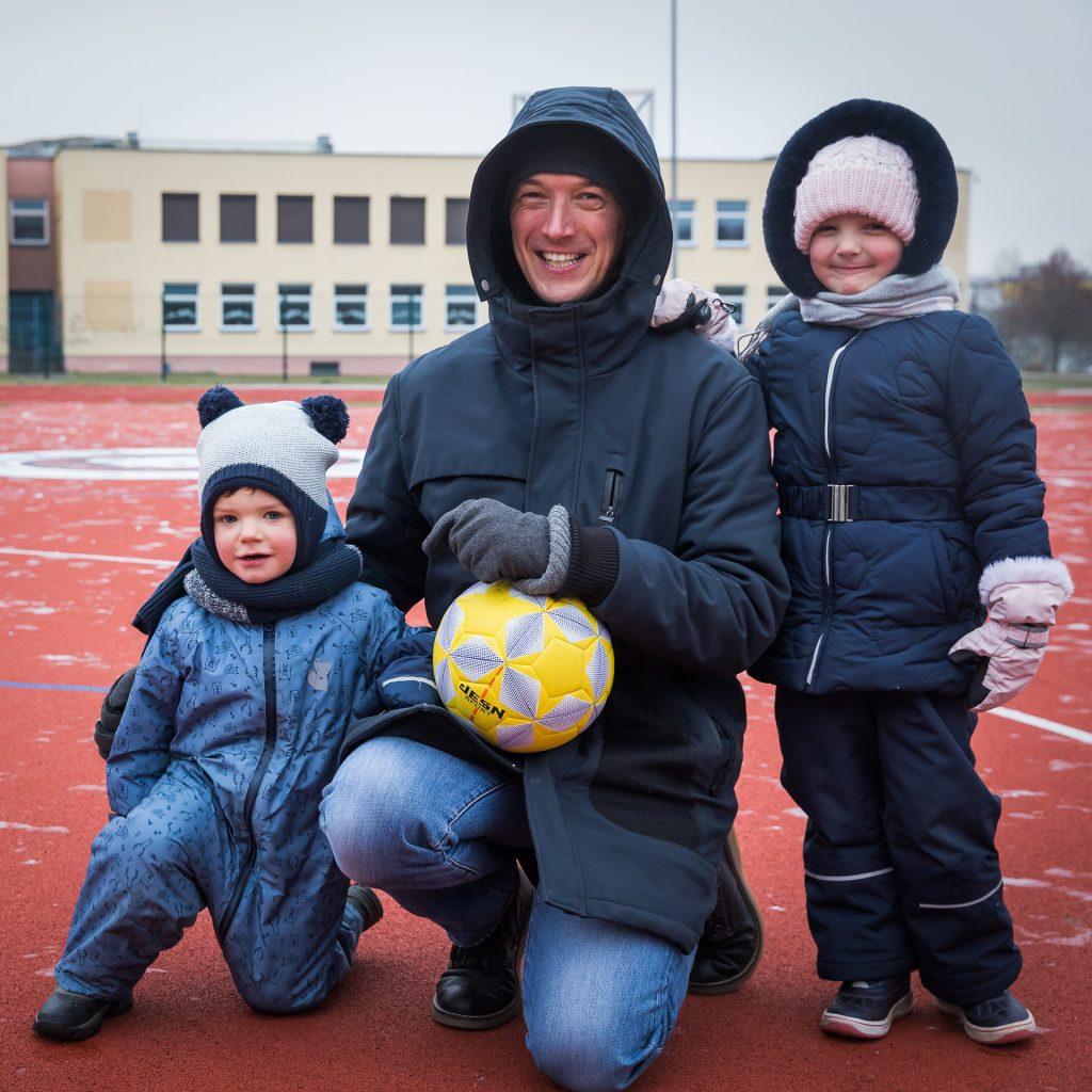 Tėtis su dviem vaikais futbolo lauke, pozuoja su kamuoliu