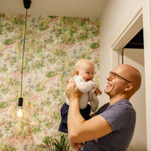 Tėtis ant rankų laiko kūdikį, abu juokiasi