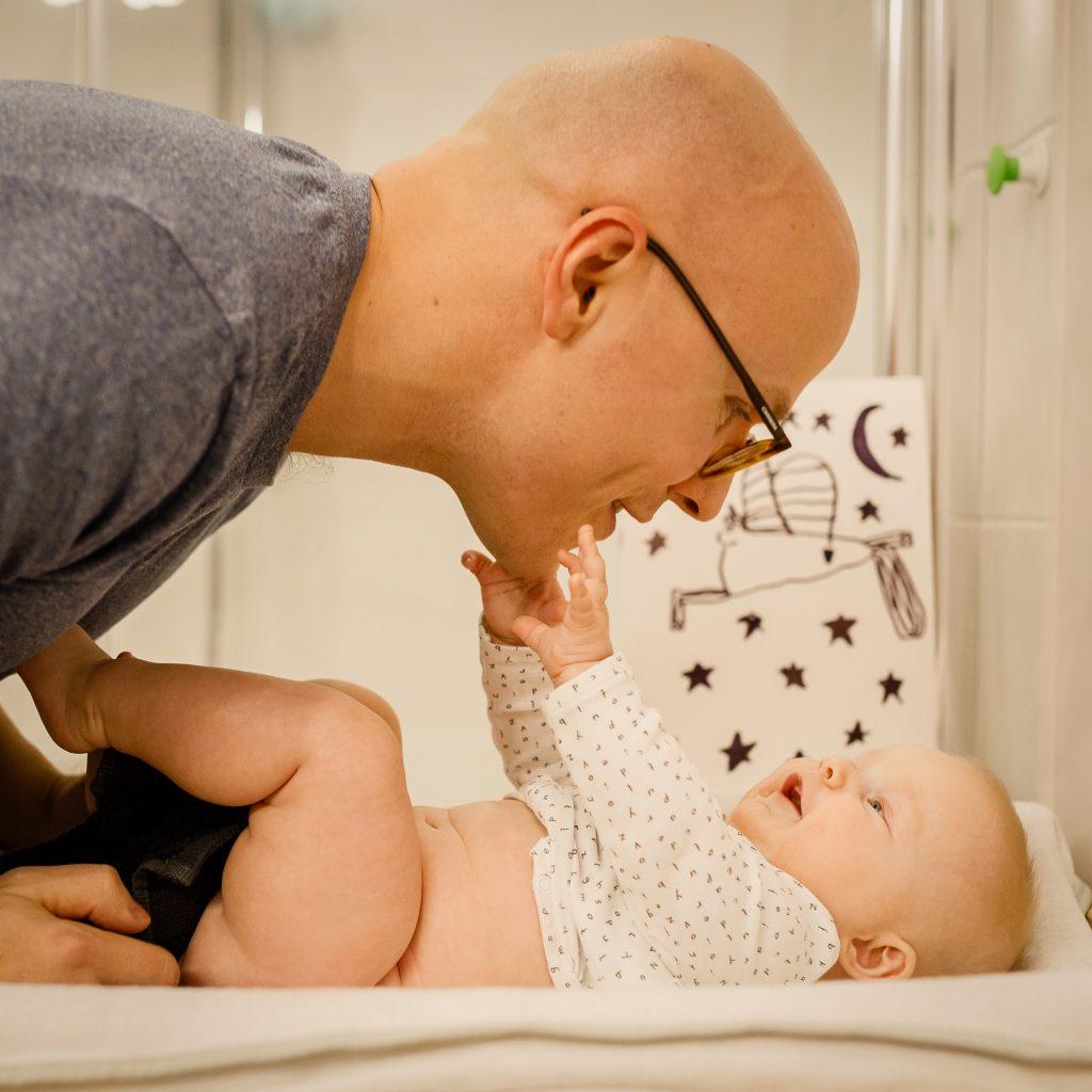 Tėtis su kūdikiu, abu šypsosi