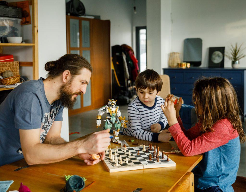 Tėtis su sūnumis žaidžia šachmatais