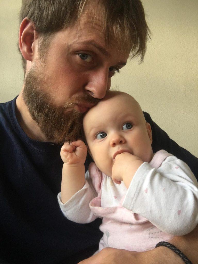 Tėtis laiko ant rankų dukrelę ir bučiuoja jai į viršugalvį
