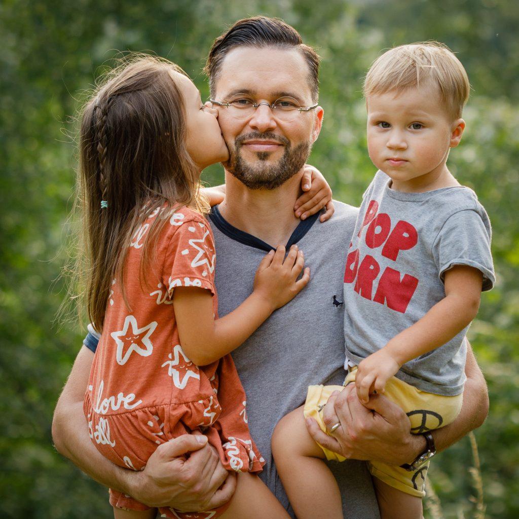Tėtis ant rankų laiko dukrą ir sūnų, dukra bučiuoja tėttį į žandą