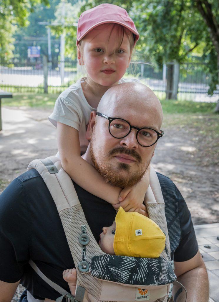 Tėtis su ketverių metų dukrele ant pečių ir kelių mėnesių dukreele ant krūtinės nešyklėje